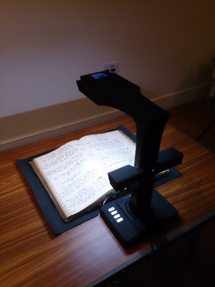 Photo of a book scanner positioned over an open book with hand-written text