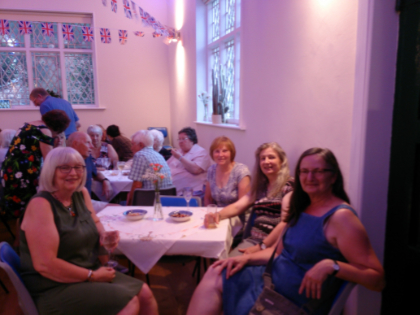 Photo of people seated at a table and smiling, inside the Old School Room hall building, Cossall