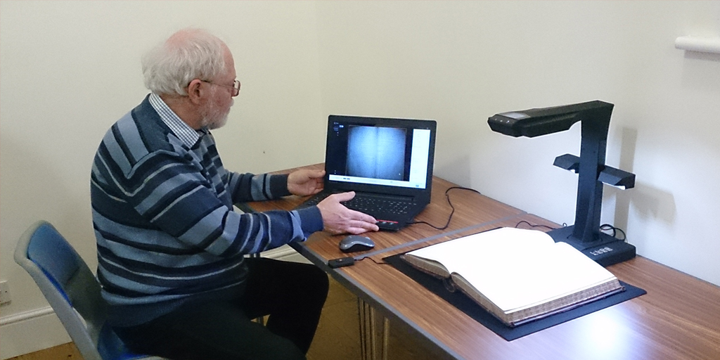 Photo of a man using a laptop computer to together with a book scanner
