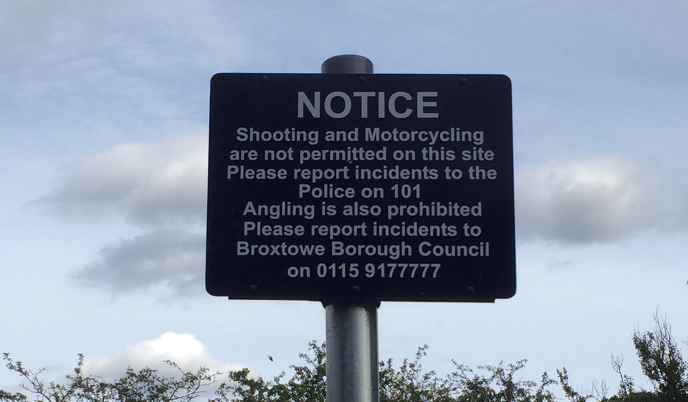 "Photo of sign reading ""Notice - shooting and motorcycling are not permitted on this site. Please report incidents to the Police on 101. Angling is also prohibited. Please report incidents to Broxtowe Borough Council on 0115 9177777"""